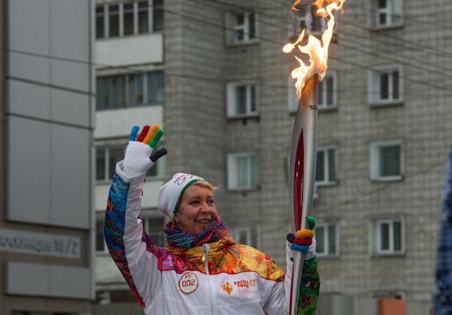 Russian popular entertainer Tatyana Lazareva holds the Olympic torch during the Olympic torch relay in Novosibirsk, about 2,800 kilometers (1,750 miles) east of Moscow, Russia, Friday, Dec. 6, 2013. The 65,000-kilometer (39,000 mile) Sochi torch relay, which started on Oct. 7, is the longest in Olympic history. The torch has traveled to the North Pole on a Russian nuclear-powered icebreaker and has even been flown into space. (AP Photo/Ilnar Salakhiev)