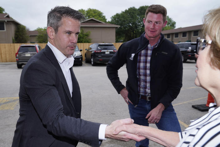 Rep. Adam Kinzinger, R-Ill., left, shakes hands with Linda Thomas right, as Texas congressional candidate Michael Wood looks on Tuesday, April 27, 2021, in Arlington, Texas. Wood is considered the anti-Trump Republican Texas congressional candidate that Kinzinger has endorsed in the May 1st special election for the 6th Congressional District. (AP Photo/LM Otero)