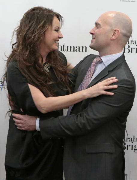 British singer Sarah Brightman, left, and Space Adventures CEO Eric Anderson embrace after a news conference in Moscow, Russia, Wednesday, Oct. 10, 2012. Brightman is to become the first-ever global recording artist to take a spaceflight, teaming up with Space Adventures for a journey to the International Space Station (ISS). (AP Photo/Mikhail Metzel)