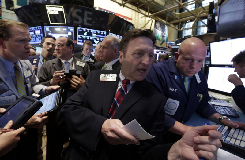 Specialist Thomas Facchine, second from right, directs trades in Metro PCS at the close of trading on the floor of the New York Stock Exchange, Tuesday, April 30, 2013. Asian stock markets fell Wednesday May 1, 2013 in holiday-thinned trading after the pace of China's manufacturing growth slowed in April, raising fears of a weaker recovery in the world's second-largest economy. Shares in other regions were poised to post gains, however. (AP Photo/Richard Drew)