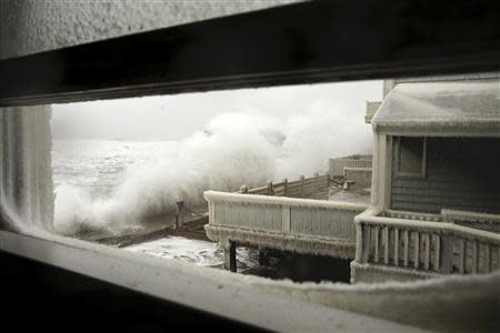 Waves crash into houses on Lighthouse Road during a winter nor'easter snow storm in Scituate, Massachusetts January 3, 2014. REUTERS/Dominick Reuter