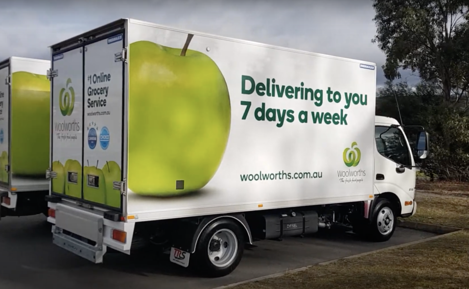 Woolworths delivery truck shown in car park.