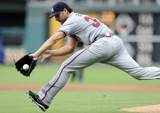 Atlanta Braves' Branon Beachy reaches for a ball hit by Philadelphia Phillies' Delmon Young in the first inning of a baseball game on Saturday, Aug. 3, 2013, in Philadelphia. (AP Photo/Michael Perez)
