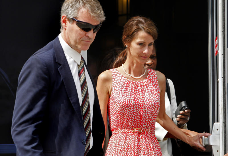 Cheri Young, right, is escorted out of the Federal Courthouse in Greensboro, N.C. on Monday, April 30, 2012, after testifying in the John Edwards trial. Young, the wife of an ex-aide to John Edwards broke down on the witness stand Monday as she recounted how the candidate asked the couple to hide an affair he was having and justified using wealthy donors' money to do it. (AP Photo/The News & Observer, Shawn Rocco)