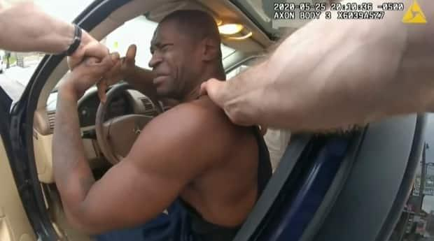 In this image from police body camera video, Minneapolis police officers attempt to remove Floyd from a vehicle, on May 25, 2020, outside Cup Foods convenience store. Floyd died after being restrained by Chauvin, who pressed a knee on his neck and back for about nine minutes, and two other officers.