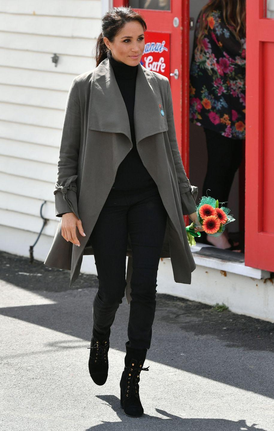 """<p>Harry and Meghan met with a young New Zealanders to discuss mental health while in Wellington. For the daytime outing, the Duchess wore Club Monaco's Ellayne Trench over a sweater by Jac + Jack with <a href=""""https://outlanddenim.ca/products/harriet-in-black-1?variant=12431424815201"""" rel=""""nofollow noopener"""" target=""""_blank"""" data-ylk=""""slk:Outland Denim's Harriet jeans."""" class=""""link rapid-noclick-resp"""">Outland Denim's Harriet jeans.</a> Meghan also wore lace-up boots by Stuart Weitzman</p><p><a class=""""link rapid-noclick-resp"""" href=""""https://go.redirectingat.com?id=74968X1596630&url=https%3A%2F%2Fshop.nordstrom.com%2Fs%2Fstuart-weitzman-veruka-lace-up-boot-women%2F4900880&sref=https%3A%2F%2Fwww.townandcountrymag.com%2Fstyle%2Ffashion-trends%2Fg3272%2Fmeghan-markle-preppy-style%2F"""" rel=""""nofollow noopener"""" target=""""_blank"""" data-ylk=""""slk:SHOP NOW"""">SHOP NOW </a><em>Veruka Lace-Up Boot by Stuart Weitzman, $698</em></p>"""