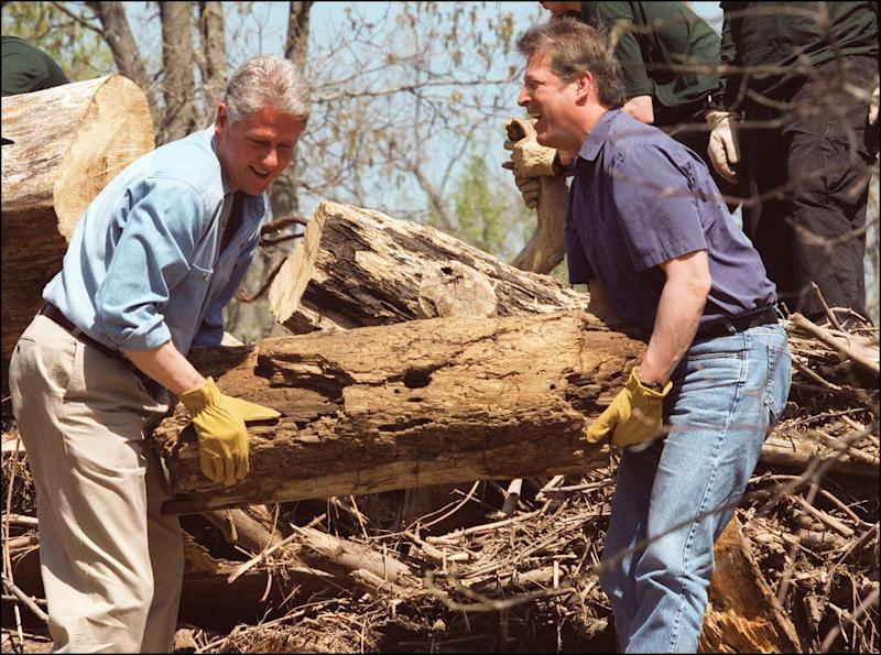 Al Gore (right) and US President Bill Clinton help volunteers at C and O Canal National Historical Park in Great Falls on April 22, 1996 to restore a canal path damaged by storms