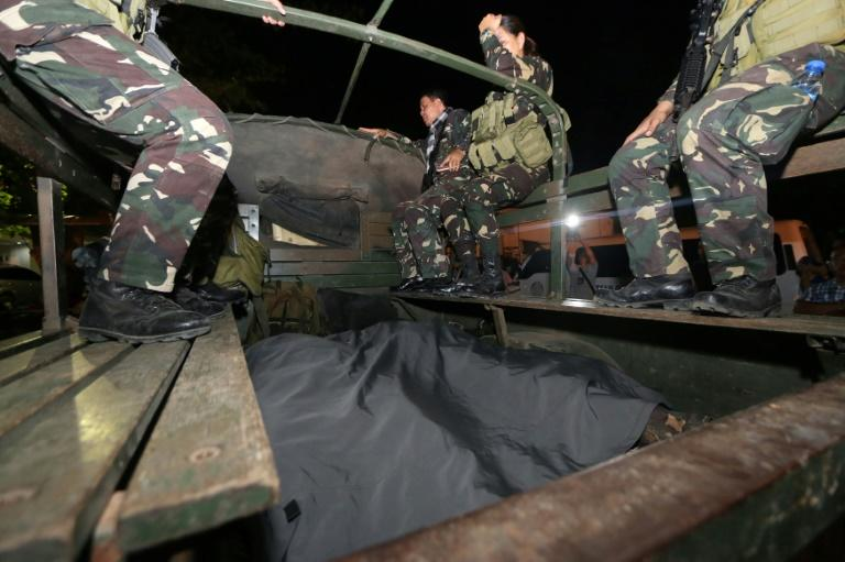Soldiers alongside the bodies of colleagues killed in clashes with militants on Bohol island