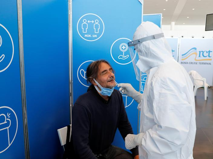 This image shows a man getting a swab from another person in a hazmat suit.