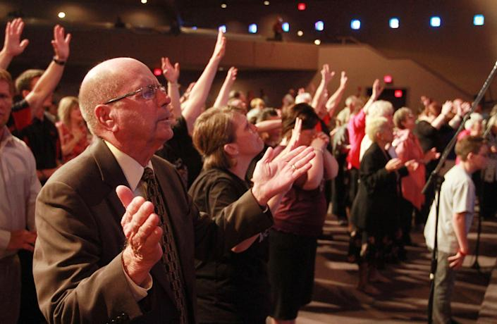In this March 25, 2012, photo, churchgoers at the Brownsville Assembly raise their hands in praise as senior pastor Rev. Evon Horton preaches to his congregation during service in Pensacola, Fla. The church that was home to the largest Pentecostal outpouring in U.S. history is on the edge of financial ruin. The revival that drew some 5,500 people nightly at its height saddled the congregation with an $11.5 million debt that members were left to pay off after both the out-of-town throngs and former Rev. John Kilpatrick moved on. The red ink is mostly unknown outside the congregation. (AP Photo/John David Mercer)