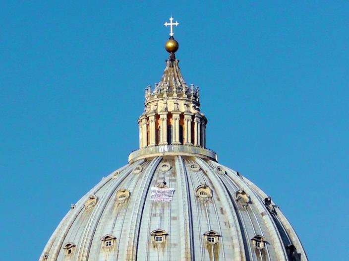 Italian businessman Marcello di Finizio stands by his banner as he protests on St. Peter's 130-meter-high (42-feet-high) dome, at the Vatican, Wednesday, Oct. 3, 2012. Di Finizio eluded Vatican security Tuesday and scaled the dome of St. Peter's Basilica to protest against the Italian government and European Union policies. Officials said Wednesday that the man, who identified himself as the owner of a beach resort, refused appeals from government ministers offering to meet with him if he would come down. (AP Photo/Paolo Santalucia)
