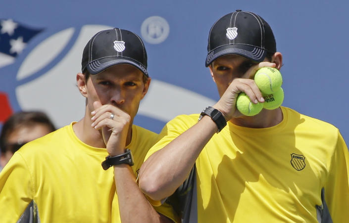 Mike, left, and Bob Bryan plan the next point against Leander Paes, of India, and Radek Stepanek, of the Czech Republic, during the men's doubles quarterfinals of the 2013 U.S. Open tennis tournament, Thursday, Sept. 5, 2013, in New York. (AP Photo/David Goldman)