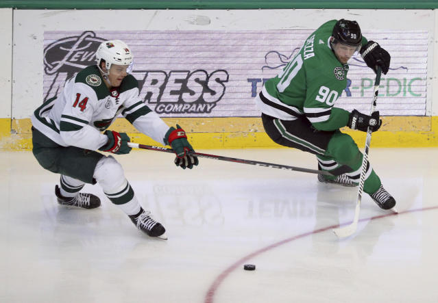 Minnesota Wild center Joel Eriksson Ek (14) and Dallas Stars center Jason Spezza (90) chase the puck in the second period of an NHL hockey game Saturday, April 6, 2019, in Dallas. (AP Photo/Richard W. Rodriguez)
