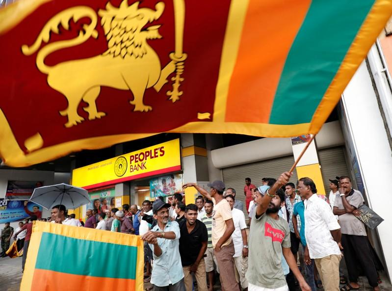 People celebrate after the voting ended during the presidential election day in Colombo