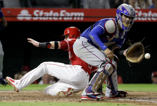 Los Angeles Angels' Taylor Ward, left, scores past Texas Rangers catcher Robinson Chirinos on a two-run double by Francisco Arcia during the second inning of a baseball game in Anaheim, Calif., Wednesday, Sept. 12, 2018. (AP Photo/Chris Carlson)