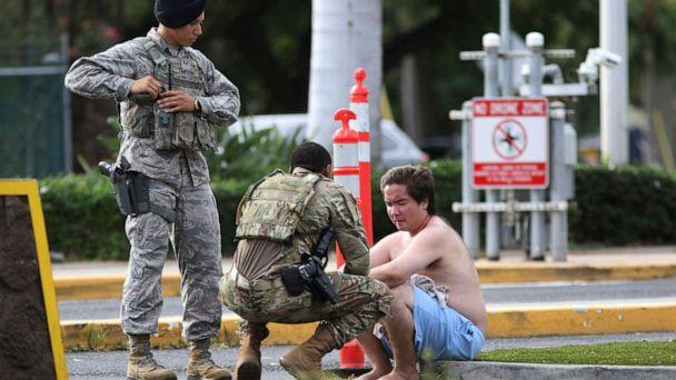 PHOTO: Security forces attend to an unidentified male outside the the main gate at Joint Base Pearl Harbor-Hickam, Dec. 4, 2019, in Hawaii, following a shooting. (Caleb Jones/AP)