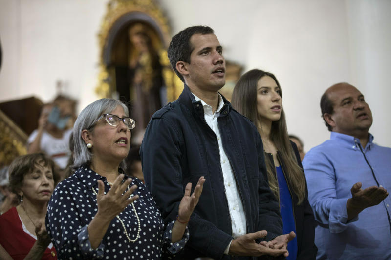 Opposition National Assembly President Juan Guaido, who declared himself interim president of Venezuela, prays next to his wife Fabiana Rosales, second from right, during Mass at a church in Caracas, Venezuela, Sunday, Jan. 27, 2019. Guaido says he is acting in accordance with two articles of the constitution that give the National Assembly president the right to hold power temporarily and call new elections. (AP Photo/Rodrigo Abd)