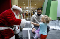 Tyler Rapsey with daughter Isabelle visits with Santa Claus, with safety protocols in place, at Capital City Mall in Lower Allen Township, Pa., on Wednesday, Nov. 11, 2020. Malls are doing all they can to keep the jolly old man safe from the coronavirus, including banning kids from sitting on his knee, completely changing what a Santa visit looks like. (Dan Gleiter/The Patriot-News via AP)