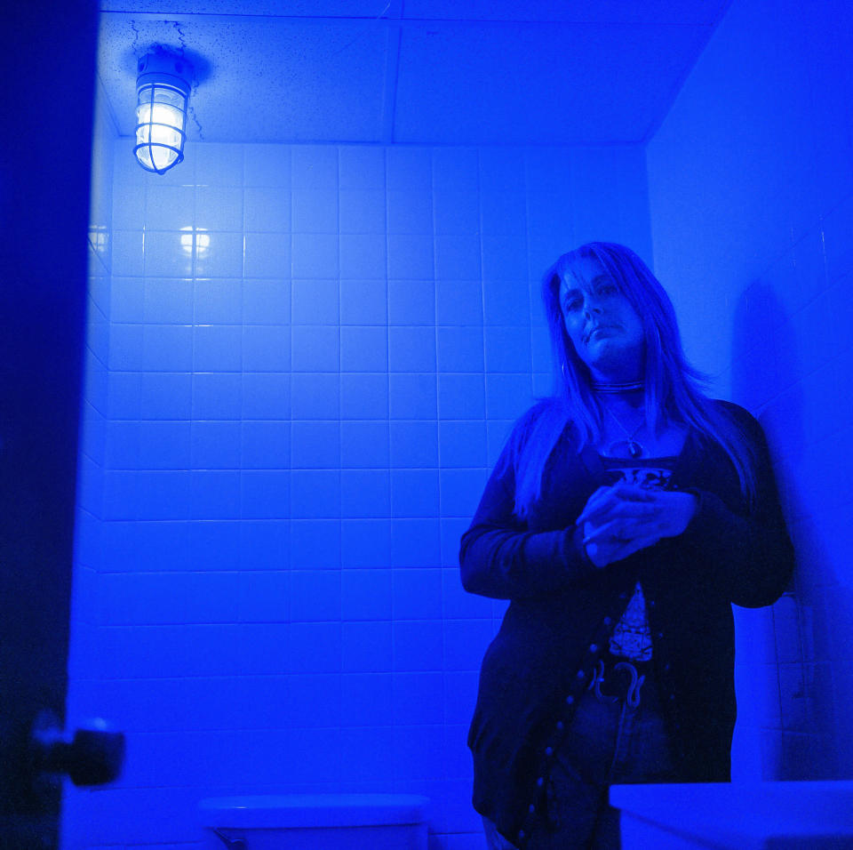 """In this photo made with a medium format film camera, Misti Mann-France stands for a portrait in a bathroom at the laundromat she manages under a blue light installed to make it harder for drug users to find a vein, Thursday, March 18, 2021, in Huntington, W.Va. Hers was among several local businesses to install blue lights at the height of the city's opioid crisis, when they would often find syringes left behind by drug users. """"It was the only thing we could think of to do to help,"""" she said. """"And it has helped tremendously."""" She said people have overdosed several times in the parking lot of their business, which includes the laundry and a video poker room. A local gas station chain and liquor store also switched to blue lights. """"I wish there was a solution to the bigger problem,"""" she said. """"There are so many out there on drugs, and it's sad, it really is."""" (AP Photo/David Goldman)"""