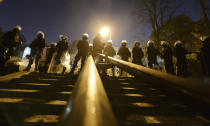Police stand guard while protesters block the parliament in Warsaw, Poland, Wednesday Oct. 28, 2020. People across Poland stayed off their jobs and huge crowds poured onto the streets for a seventh straight day of protests Wednesday, enraged over a top court ruling that bans abortions in cases of fetal abnormalities. (AP Photo/Czarek Sokolowski)