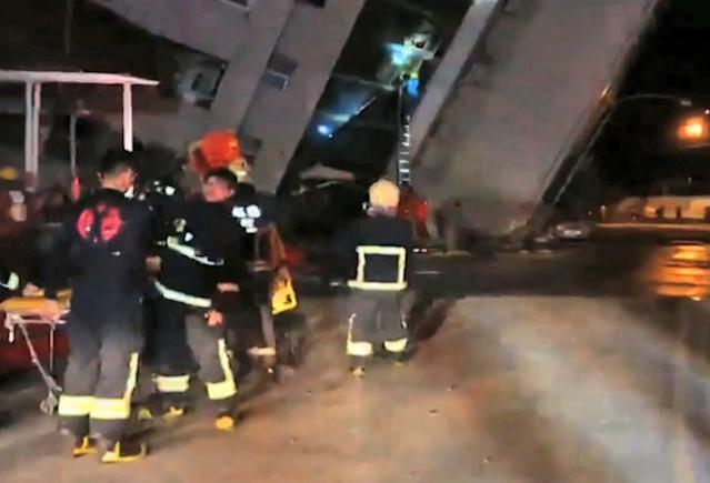 <p>In this image from TV, emergency services attend after a building collapsed on its side, as a man climbs a ladder to gain access to the building, centre background, after an early morning earthquake in Hualien County, eastern Taiwan, Feb. 7 2018. (Photo: EBC via AP) </p>