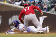 Chicago Cubs' Javier Baez slides into second for a steal attempt and is called out by second base umpire Joe West as Cincinnati Reds' Kyle Farmer comes off the tag during the fourth inning of a baseball game Friday, May 28, 2021, in Chicago. The call was overturned after video review. (AP Photo/Charles Rex Arbogast)