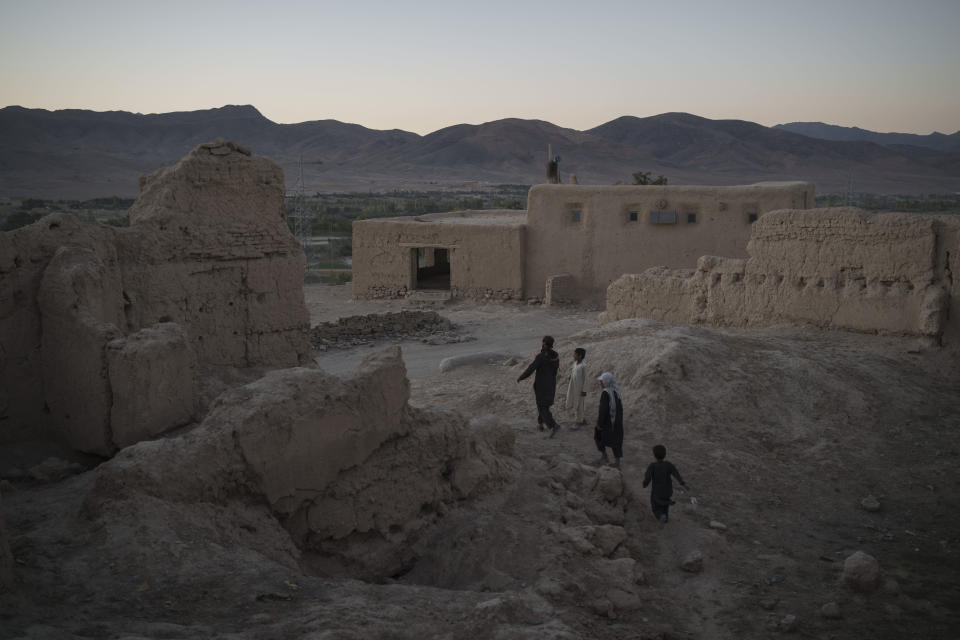 Afghans walk among the rubble of houses destroyed by fighting at a village in Wardak province, Afghanistan, Tuesday, Oct. 12, 2021. (AP Photo/Felipe Dana)