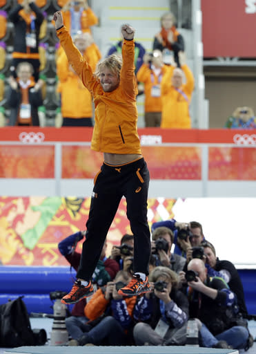 Photographers huddle in the background taking pictures of gold medallist Michel Mulder from the Netherlands as he jumps in celebration during the flower ceremony for the men's 500-meter speedskating race at the Adler Arena Skating Center at the 2014 Winter Olympics, Monday, Feb. 10, 2014, in Sochi, Russia. (AP Photo/David J. Phillip)