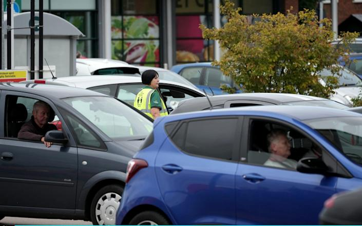A store worker directs traffic as people queue for petrol at a Morrisons in Ellesmere Port, Cheshire - Christopher Furlong/Getty Images Europe