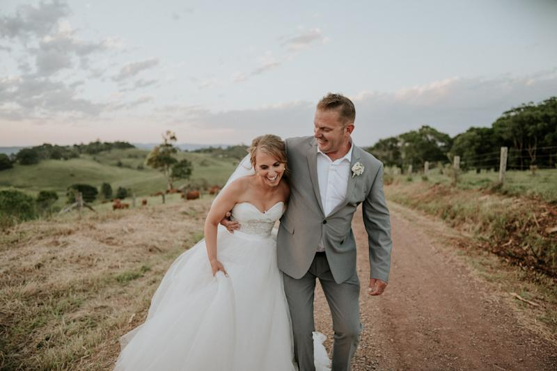 The bride and groom stand together laughing on a dirt road with green hills and a pale blue, partly cloudy sky behind them. The groom has his arm wrapped around the bride's waist as she holds her skirt in one hand. (James Day Photography)