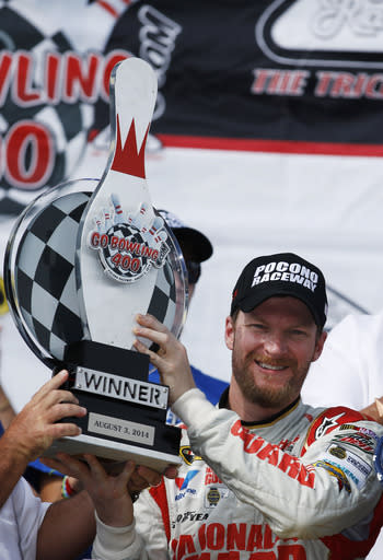 Dale Earnhardt Jr. poses with the trophy in Victory Lane after winning the NASCAR Sprint Cup Series auto race at Pocono Raceway, Sunday, Aug. 3, 2014, in Long Pond, Pa. (AP Photo/Matt Slocum)