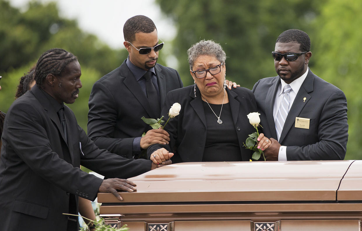 Sharon Risher and Gary Washington, left, stand over the casket of their mother, Ethel Lance, following her burial service. Lance was one of nine people killed in the shooting at Emanuel AME Church in Charleston, S.C., on June 25, 2015. (Photo: David Goldman/AP)
