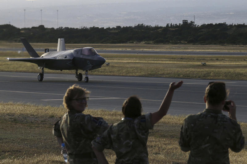 FILE - In this Tuesday, May 21, 2019 file photo, Soldiers wave at a F-35B aircraft waves after landing at Akrotiri Royal air forces base near coastal city of Limassol, Cyprus. Britain's defense secretary said the country's most advanced military aircraft, the Lightning F-35B, that is undergoing training at a British air base in Cyprus has flown its first missions over Syria and Iraq as part of the ongoing operations against the Islamic State group, in a statement issued Tuesday June 25, 2019. (AP Photo/Petros Karadjias, File)