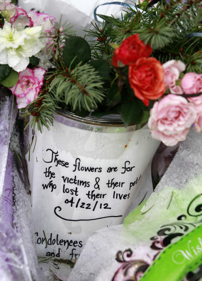 Flowers sit as a make-shift shrine outside the burned-out home where a gun-toting survivalis is suspected of killing his wife and daughter several days earlier Friday, April 27, 2012, in North Bend, Wash. Peter Alex Keller may be holed up in a self-made fort not far from where Seattle's outer suburbs give way to the vast recreational playground of Cascade Mountains. Police expect more people to hit the nearby trails this weekend, and deputies are warning them to steer clear of Keller if they think they see him. (AP Photo/Elaine Thompson)