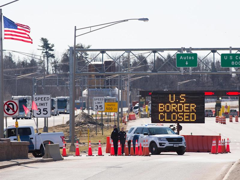 US Customs officers stand beside a sign saying that the US border is closed at the US/Canada border in Lansdowne, Ontario, on 22 March 2020: (2020 Getty Images)