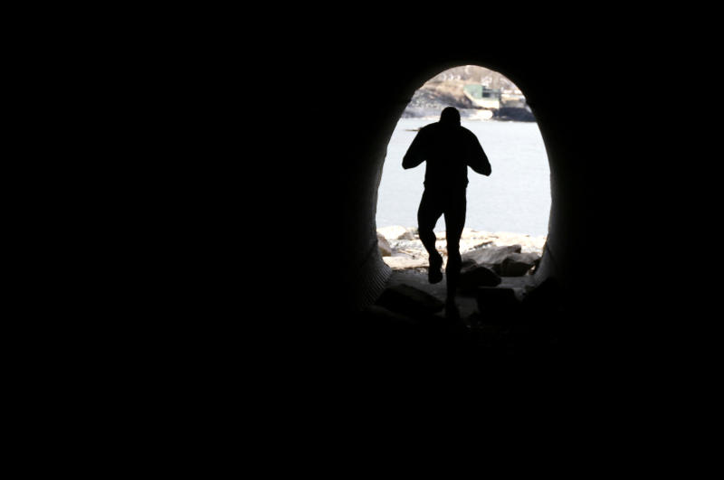 FILE - In this Wednesday, March 27, 2013 file photo, a runner exits a tunnel that is part of the Cliff Walk, in Newport, R.I. The Cliff Walk is one of a number of free attractions in Rhode Island that can be visited in the Summer. (AP Photo/Steven Senne, File)