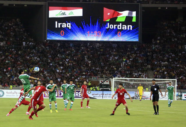 FILE - In this Thursday, June 1, 2017 file photo, Iraq, in green, in action against Jordan, in red, during their friendly football match in Basra, southeast of Baghdad, Iraq. FIFA says on Tuesday, Aug. 20, 2019 the southern Iraqi city of Basra can host the national teams return to playing World Cup qualifying games at home. Security concerns since the 1980s have forced Iraq to host most qualifiers in neutral countries. (AP Photo/Nabil al-Jourani, file)