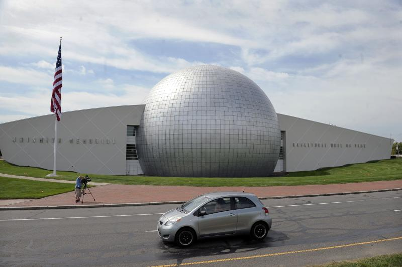 FILE - In this Sept. 8, 2016, file photo, a car passes The Naismith Memorial Basketball Hall of Fame in Springfield, Mass. The Hall of Fame was gearing up for a great year: not just the certain election of NBA superstars like Kobe Bryant, Kevin Garnett and Tim Duncan, but also a chance to unveil a completely renovated museum. Because of the coronavirus outbreak, the reopening has been pushed back two months to July 1 and the induction ceremony is being postponed, either to October or the spring. (AP Photo/Jessica Hill, File)