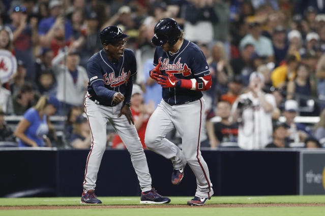 Atlanta Braves' Josh Donaldson, right, is greeted by third base coach Ron Washington after hitting a home run during the eighth inning of the team's baseball game against the San Diego Padres on Friday, July 12, 2019, in San Diego. (AP Photo/Gregory Bull)