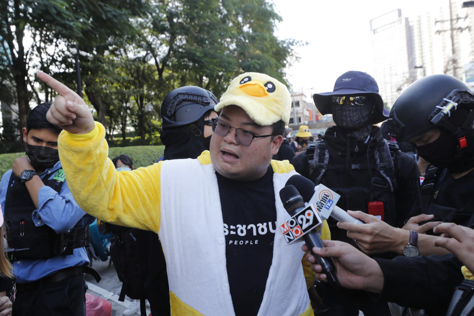 "Protest leader Parit ""Penguin"" Chiwarak speaks to the media while wearing an outfit of a yellow duck, which has become a good-humored symbol of resistance during anti-government rallies, Wednesday, Nov. 25, 2020, in Bangkok, Thailand. Thai authorities have escalated their legal battle against the students leading pro-democracy protests, charging 12 of them with violating a harsh law against defaming the monarchy. (AP Photo/Sakchai Lalit)"