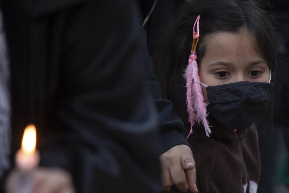 A young girl attends a vigil in Toronto on Sunday May 30, 2021, for the 215 Indigenous children, whose remains were uncovered on the grounds of a former residential school near Kamloops, British Columbia. The discovery of a mass grave was announced late on Thursday by the Tk'emlups te Secwépemc people after the site was examined by a team using ground-penetrating radar. (Chris Young/The Canadian Press via AP)