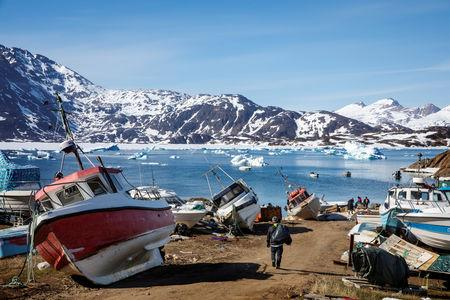 FILE PHOTO: A man walks to his boat past a number of abandoned and dry-docked boats in the town of Tasiilaq, Greenland, June 15, 2018. REUTERS/Lucas Jackson/File Photo