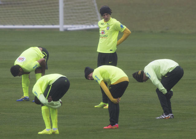 Brazil's David Luiz stands on the pitch as teammates stretch their muscles during a practice session at the Granja Comary training center in Teresopolis, Brazil, Friday, July 11, 2014. Brazil will face the Netherlands in the World Cup third-place match Saturday. (AP Photo/Leo Correa)