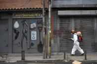 A city worker sprays disinfectant on shuttered storefronts in the Catia neighborhood of Caracas, Venezuela, Saturday, Aug. 8, 2020, amid the new coronavirus pandemic. (AP Photo/Matias Delacroix)