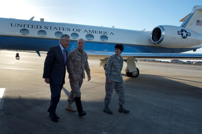 FILE PHOTO: Handout photo of then U.S. Secretary of Defense Hagel walks with Vice Admiral Harward (C) and Colonel Martin, vice commander of 6th Air Mobility Wing, after landing at MacDill Air Force Base, Tampa