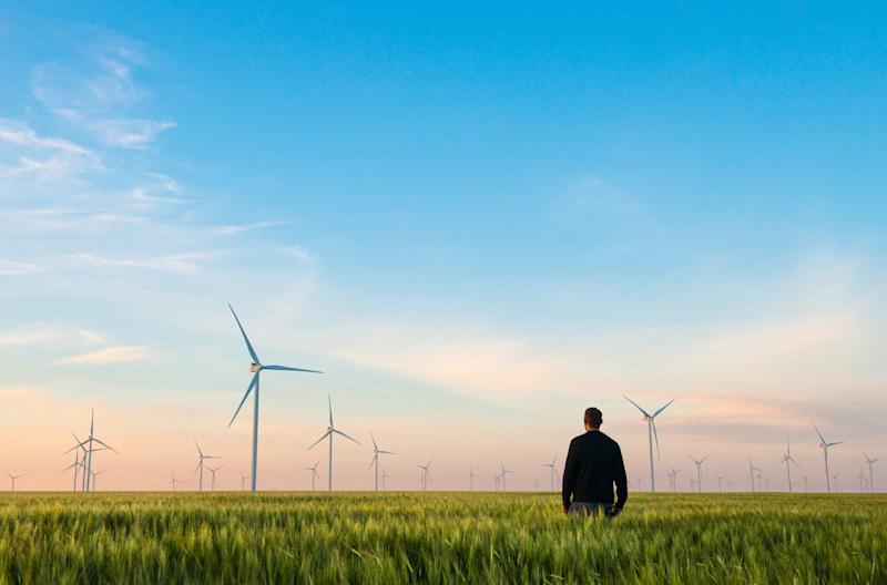 A man in a green field with wind turbines in the background.