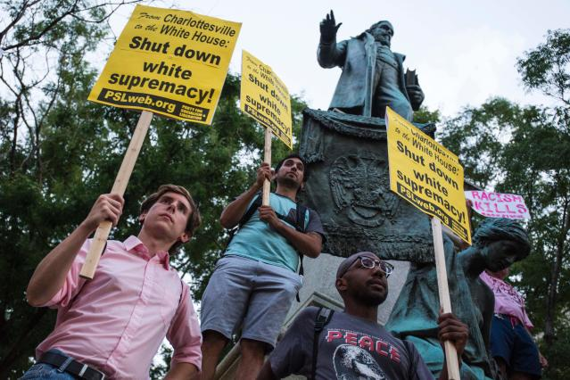 "<p>Demonstrators hold signs while standing in front of the statue of Confederate General Albert Pike on August 13, 2017 in Washington, D.C., the only member of the Confederate military with an outdoor statue in the U.S. capital, during a vigil in response to the death of a counter-protestor in the August 12 ""Unite the Right"" in Charlottesville, Va. (Photo: Zach Gibson/AFP/Getty Images) </p>"