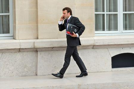 FILE PHOTO: French President's councillor Emmanuel Macron talks on a mobile phone as he arrives to attend a meeting at the OECD headquarters in Paris
