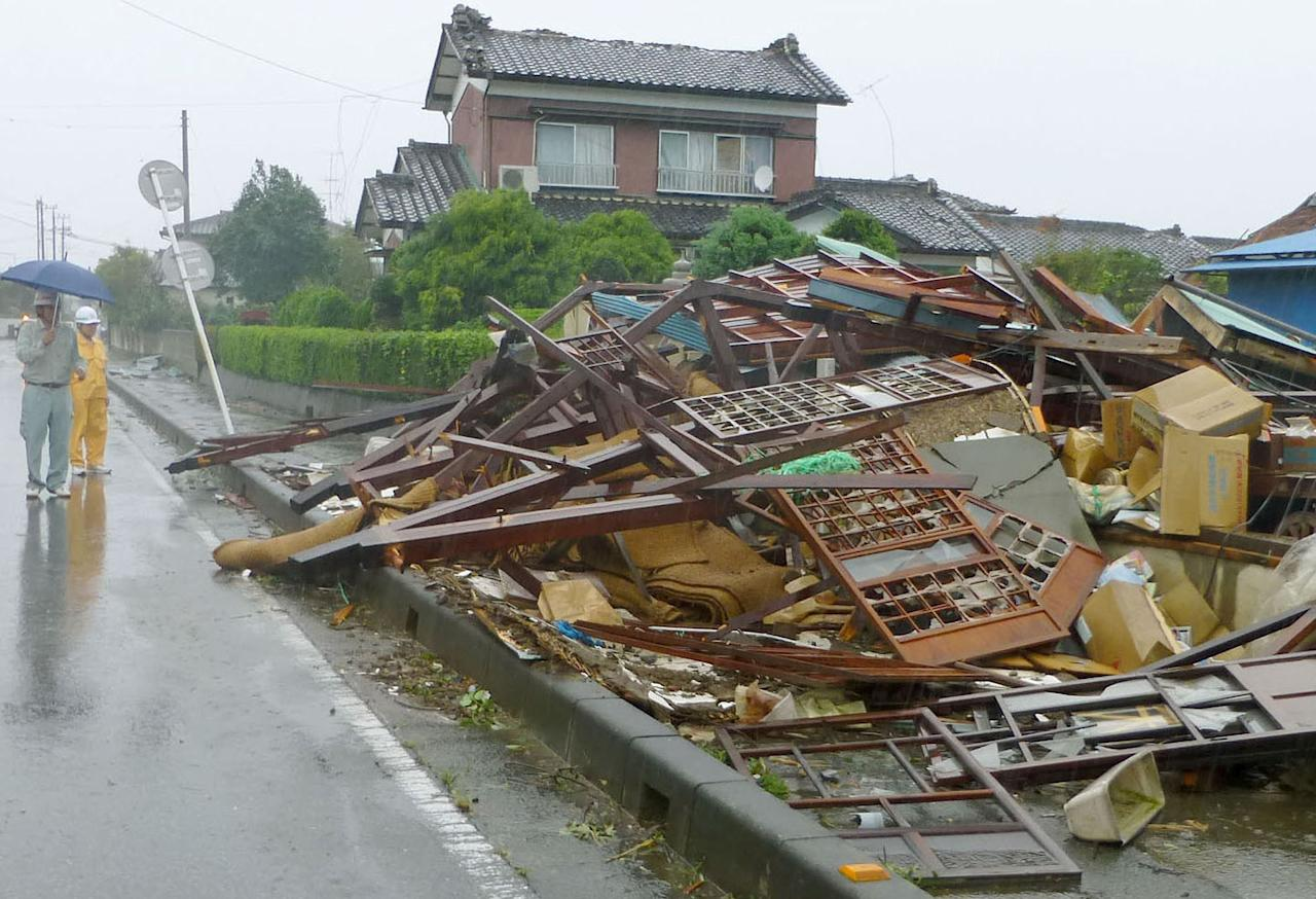 City officials look on a house destroyed by a strong wind caused by an approaching typhoon in Kumagaya, Saitama Prefecture, north of Tokyo, Monday, Sept. 16, 2013. Typhoon Man-yi, one of the most powerful storms to lash Japan this season, was bearing down on Japan and went past Tokyo on Monday, leaving one dead and dumping torrential rains, damaging homes and flooding parts of the country's popular tourist destination of Kyoto, where hundreds of thousands of people were ordered to evacuate to shelters. (AP Photo/Kyodo News) JAPAN OUT, CREDIT MANDATORY