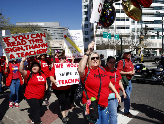 <p>Theresa Lafay, a special education teacher in the Denver Public Schools, leads a chant as she and fellow teachers march during a rally Friday, April 27, 2018, in Denver, Colo. (Photo: David Zalubowski/AP) </p>
